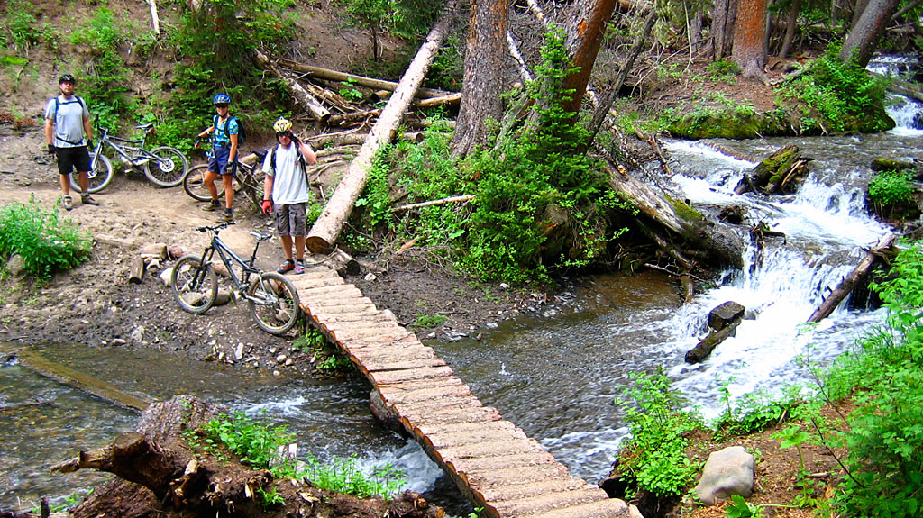 Mark, Carol and John at a creek crossing. John salutes and Mark inhales.