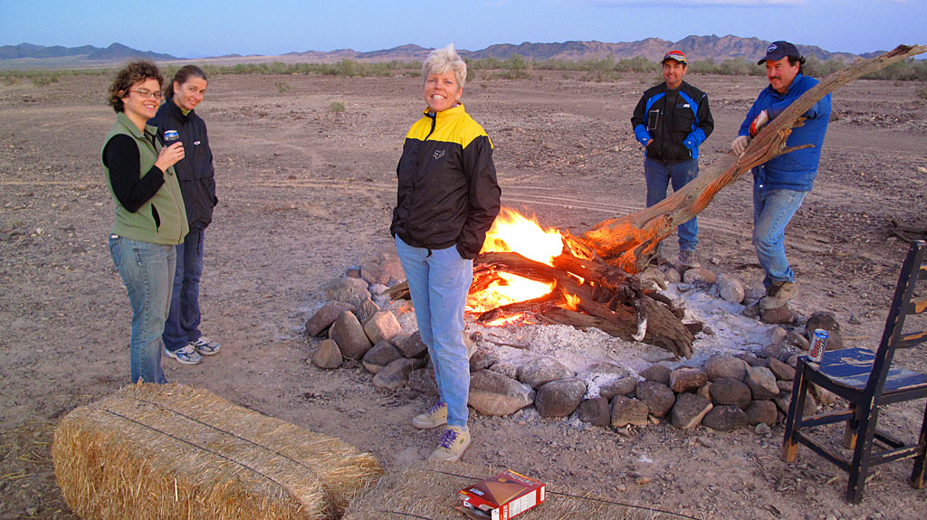 Robert and Henri stoke the fire while Sandy, KT and Carol try to keep warm.