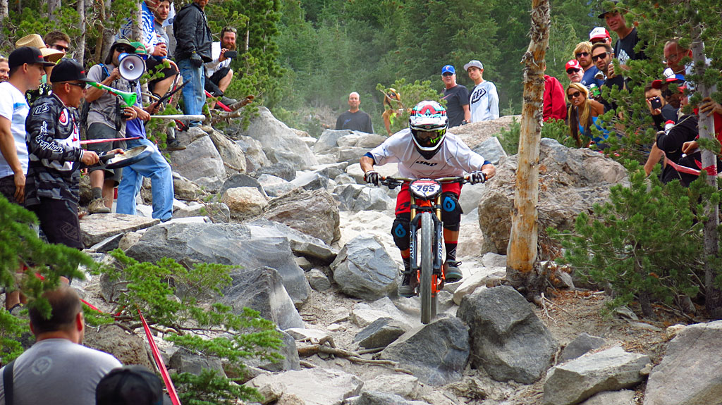 """Men's Pro Downhill at a <a title=""""Google Maps"""" href=""""http://goo.gl/maps/L91Lq"""" target=""""_blank"""">nasty rock garden</a> just below the top of Chair 16. As always, the photos don't do justice to the speed or steepness of the trail, or the skill of the rider. The guy with the megaphone on the left was very, very """"enthusiastic,"""" if you catch our drift."""