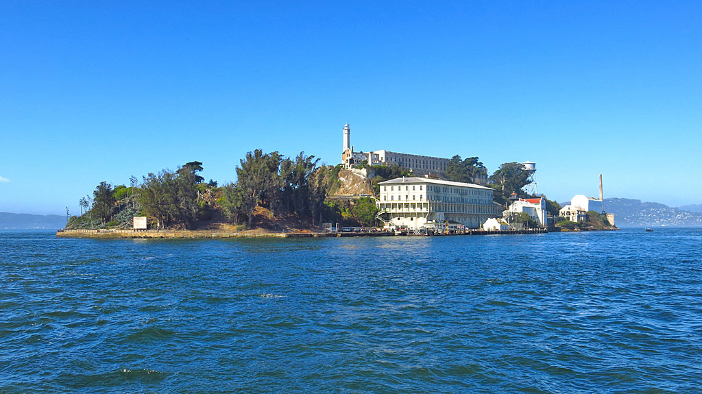 """Alcatraz is 1.5 miles into the San Francisco Bay first documented by Spanish explorers in 1775 who named the island """"La Isla de los Alcatraces"""" (The Island of the Pelicans). It stands 135 feet out of the water and was a military garrison, then a military prison, then a federal penitentiary, and now part of the National Park System."""