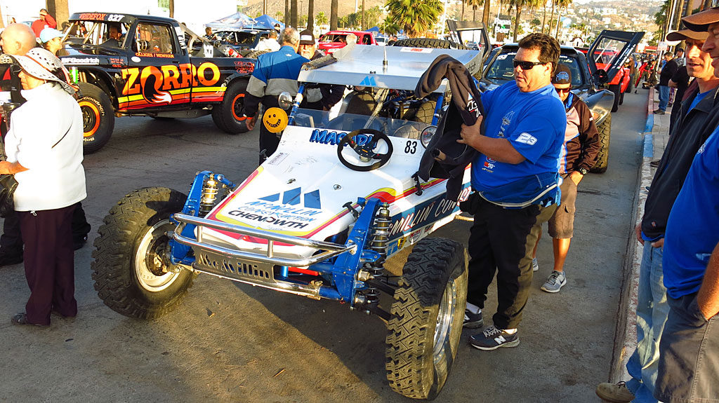 "Mark McMillian's Baja-winning #83 1979 Chenowth Class 2 car. When one of the COPS Crew Members walked past, Mark called him over and bragged, ""Hey, you guys don't have one of these.\"" He pushed a button on his dash and a digital read-out said \""Beer me! Beer me!\"""