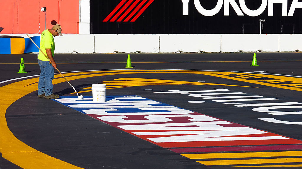 The night before the main event, track workers touched-up paint on the infield signs. The rumble strips near the turns were covered with black tire marks from the day's practice, so they were getting their own fresh paint.
