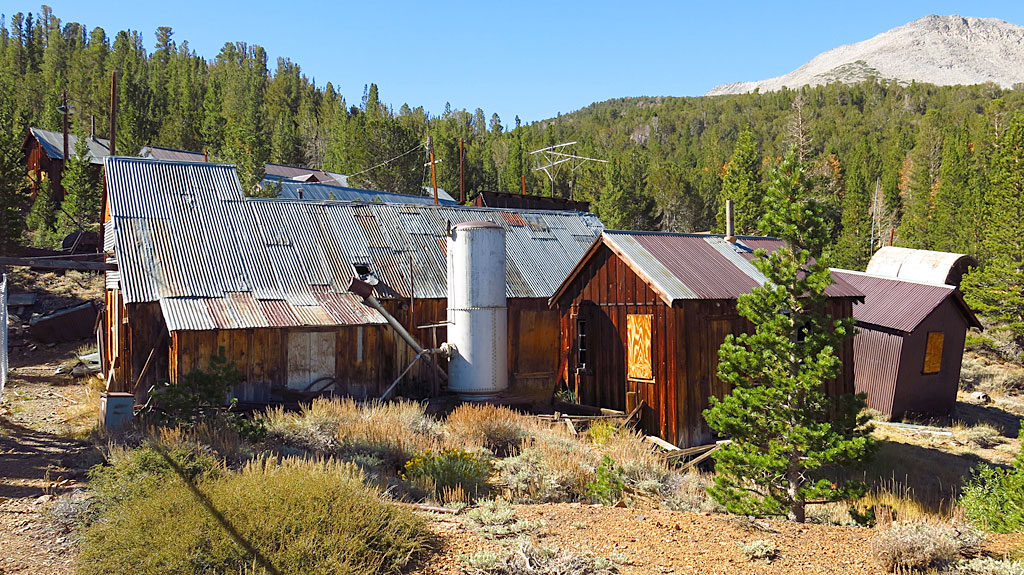 The hoist house and assay shack are adjacent to the headframe, with most of their equipment intact.